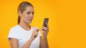 Привлекательный женский перечисляя смартфон, удивленный новым приложением онлайн сток-видео