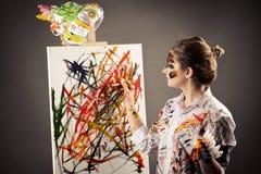 Привлекательный женский художник с красками в руках и холст изолированный на сером цвете стоковые фото