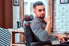 Привлекательный задумчивый человек ждет его поворот для того чтобы получить стрижку на занятой парикмахерскае стоковое фото rf