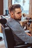 Привлекательный задумчивый человек ждет его поворот для того чтобы получить стрижку на занятой парикмахерскае стоковое изображение rf