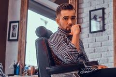 Привлекательный задумчивый человек ждет его поворот для того чтобы получить стрижку на занятой парикмахерскае стоковая фотография