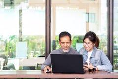 Привлекательный зрелый азиатский человек с белой стильной короткой бородой смотря ноутбук с подростковой женщиной хипстера стекел стоковые изображения rf