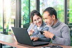Привлекательный зрелый азиатский человек с белой стильной короткой бородой смотря ноутбук с подростковой женщиной хипстера стекел стоковые изображения