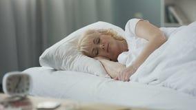 Привлекательный зрелый женский спать в ее кровати, отдыхает дома, здоровый образ жизни сток-видео