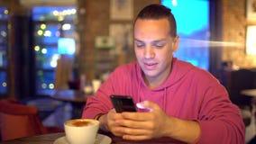 Привлекательный испанский человек бизнесмен, студент или запуск с привлекательной улыбкой используя мобильный телефон красиво видеоматериал