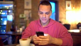 Привлекательный испанский человек бизнесмен, студент или запуск с привлекательной улыбкой используя мобильный телефон красиво сток-видео