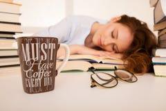 Привлекательный красивый утомленный студент спит на куче книг с Стоковые Фотографии RF