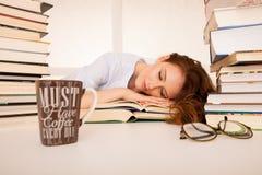 Привлекательный красивый утомленный студент спит на куче книг с Стоковые Изображения