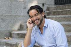 Привлекательный латинский человек на говорить лестницы города счастливый на мобильном телефоне смотря удовлетворяемый и уверенно стоковые изображения