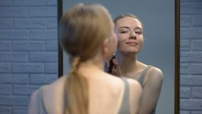 Привлекательный молодой женский применяясь фронт порошка стороны зеркала, усмехаясь на камере акции видеоматериалы