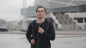 Привлекательный молодой человек бежать outdoors нося замедленное движение наушников Он смотря в камеру Дождливая погода Cardio сток-видео