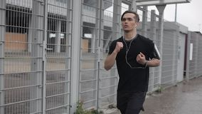 Привлекательный молодой человек бежать outdoors нося замедленное движение наушников Дождливая погода Cardio разминка тренировки r сток-видео