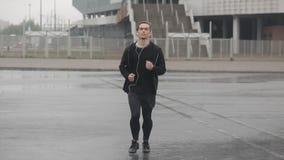 Привлекательный молодой человек бежать outdoors нося замедленное движение наушников Дождливая погода Cardio разминка тренировки r видеоматериал