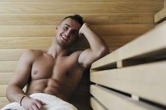 Привлекательный молодой человек в sauna стоковое фото