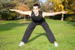 Привлекательный молодой человек делая тренировку в парке стоковое изображение