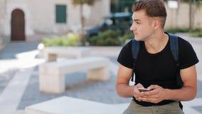 Привлекательный молодой человек с рюкзаком используя телефон сидя в конце портрета старой технологии города занятом вверх по совр сток-видео