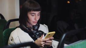 Привлекательный переход молодой женщины публично используя мобильный телефон Она отправка SMS, проверяя почты, болтовню или новос видеоматериал