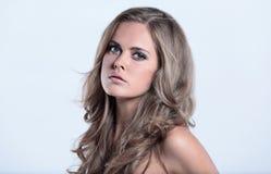 Привлекательный портрет женщины на сером брюнет предпосылки смотря стоковые фото