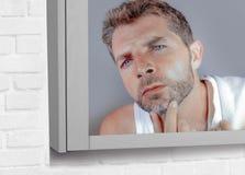 Привлекательный потревоженный и, который отнесенный кавказский человек смотря зеркало ванной комнаты находя более серые волосы в  Стоковые Фотографии RF
