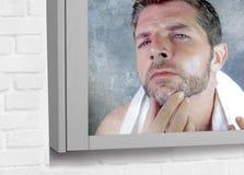 Привлекательный потревоженный и, который отнесенный кавказский человек смотря зеркало ванной комнаты находя более серые волосы в  Стоковые Фото