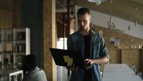 Привлекательный сконцентрированный молодой бизнесмен идет с ноутбуком в его руке и печатать Кавказский положительный человек акции видеоматериалы