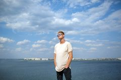 Привлекательный собрат в белой футболке и солнечных очках стоя на речном береге на запачканной естественной предпосылке Стоковые Изображения RF