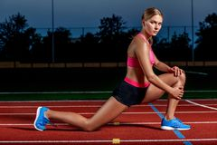 Привлекательный спортсмен молодой женщины протягивая ноги на стадионе Стоковые Фото