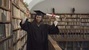 Привлекательный студент в академичном платье имеет потеху, стоя в библиотеке видеоматериал