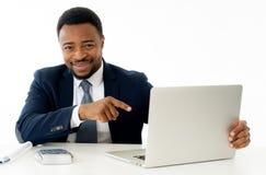 Привлекательный счастливый красивый Афро-американский бизнесмен работая на ноутбуке на столе на офисе стоковое фото