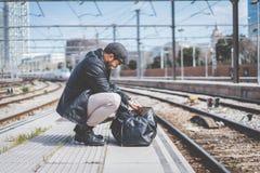 Привлекательный уверенно испанский человек имея фронт рюкзака его с сумкой одежд, идя около платформы на поезде Стоковые Фото