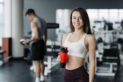 Привлекательный усмехаться и питьевая вода девушки спорта пока стоящ на спортзале с тренировкой мальчика на предпосылке стоковое фото rf