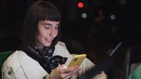 Привлекательный усмехаясь переход молодой женщины публично используя мобильный телефон Она отправка SMS, проверяя почты, болтовня сток-видео