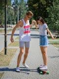 Привлекательный усмехаясь собрат уча катанию девушки на longboard в парке на естественной запачканной предпосылке Стоковые Фотографии RF