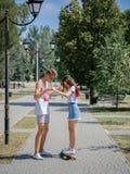 Привлекательный усмехаясь собрат уча катанию девушки на longboard в парке на естественной запачканной предпосылке Стоковое Изображение RF