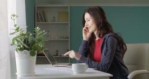 Привлекательный фрилансер женщины брюнета работая от домашнего компьютера и говоря по телефону радуясь успех с продажами