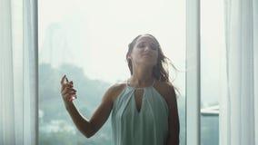 Привлекательный халат маленькой девочки распыляет благоухание духов на панорамной предпосылке окна с видом на город и стоковое фото rf