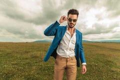 Привлекательный человек в костюме аранжирует его солнечные очки пока стоящ ou стоковое фото rf