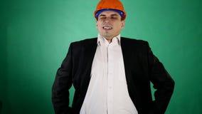 Привлекательный человек в оранжевых шлеме и костюме конструкции смотрит камеру Молодой работник показывает жесты с его видеоматериал