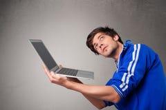 Привлекательный человек держа современную тетрадь стоковое изображение