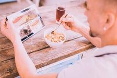 Привлекательный человек имея завтрак в кухне стоковые фото