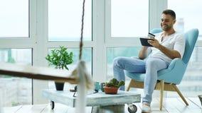 Привлекательный человек используя цифровую таблетку сидя в стуле на балконе в квартире просторной квартиры современной Стоковое Фото