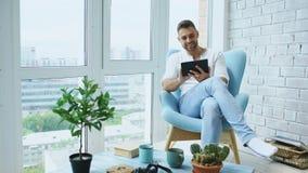 Привлекательный человек используя цифровую таблетку сидя в стуле на балконе в квартире просторной квартиры современной Стоковое Изображение