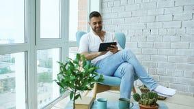 Привлекательный человек используя цифровую таблетку сидя в стуле на балконе в квартире просторной квартиры современной Стоковая Фотография RF