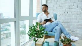 Привлекательный человек используя цифровую таблетку сидя в стуле на балконе в квартире просторной квартиры современной Стоковое Изображение RF