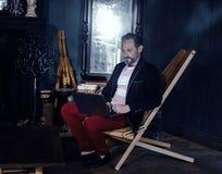 Привлекательный человек сидит на ноутбуке в темноте независимо стоковое фото rf