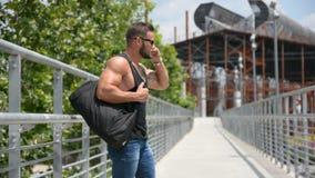 Привлекательный muscleman используя сотовый телефон видеоматериал