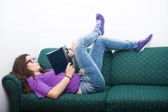Привлекательный storybook чтения девушки на кресле дома Стоковая Фотография