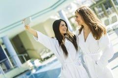 2 привлекательных дамы принимая selfie рядом с бассейном Стоковое Изображение