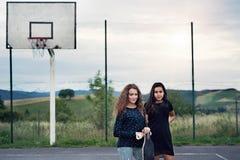 2 привлекательных девочка-подростка outdoors на спортивной площадке Стоковые Фото