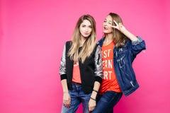 2 привлекательных девушки имея потеху, показывающ жестами мир и представлять Стоковое фото RF